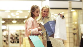 Happy young women with shopping bags in mall. Sale, consumerism and people concept - happy young women showing content of shopping bags in mall stock video