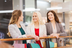 Happy young women with shopping bags in mall Royalty Free Stock Photo