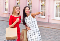 Happy young women with shopping bags pointing finger somewhere. On old city background. Sale, consumerism and people concept Stock Photo