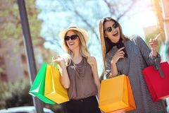 Happy young women with shopping bags pointing finger to shop window. In city Stock Image