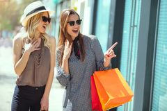 Happy young women with shopping bags pointing finger to shop window. In city Royalty Free Stock Images