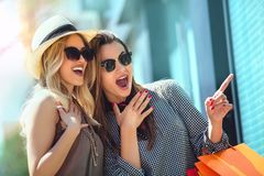 Happy young women with shopping bags pointing finger to shop window. In city Stock Photo