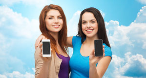 Happy young women showing smartphones screens. Advertisement, cloud computing, people and modern technology concept - two smiling teenage girls or young women Royalty Free Stock Photos