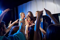 Happy young women singing karaoke in night club. Party, holidays, celebration, nightlife and people concept - happy young women singing karaoke in night club Stock Photos