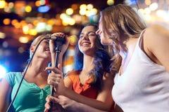 Happy young women singing karaoke in night club Stock Image