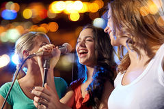 Happy young women singing karaoke in night club Royalty Free Stock Photos