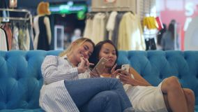 Happy young women with smartphones and shopping bags talking in mall. Professional shot in 4K resolution. 103. You can use it e.g. in your commercial video stock footage