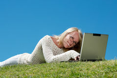 Happy young woman smiling and working on a laptop Stock Photo