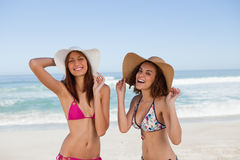 Happy young women standing on the beach Royalty Free Stock Photos