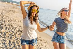 Happy young women strolling along coastline on a sunny day. Two female friends walking together on a beach, enjoying royalty free stock photos