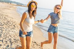Happy young women strolling along coastline on a sunny day. Two female friends walking together on a beach, enjoying royalty free stock image