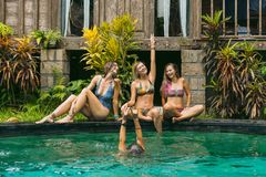 Happy young women in swimwear having fun. Near swimming pool stock images