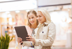 Happy young women with tablet pc and shopping bags Stock Photography