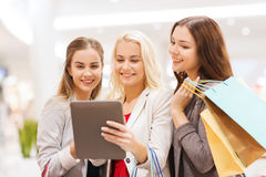 Happy young women with tablet pc and shopping bags. Sale, consumerism, technology and people concept - happy young women with tablet pc and shopping bags in mall Royalty Free Stock Images