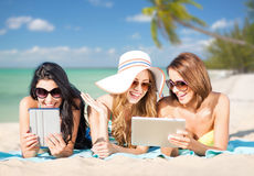 Happy young women with tablet pc on summer beach Stock Photos