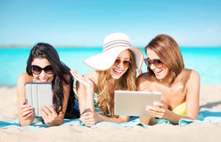 Happy young women with tablet pc on summer beach Stock Photography