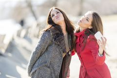 Happy young women taking photo with mobile phone Stock Photography