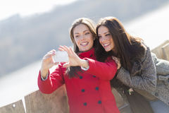 Happy young women taking photo with mobile phone Royalty Free Stock Photos