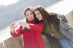 Happy young women taking photo with mobile phone Royalty Free Stock Images