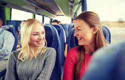 Happy young women talking in travel bus. Transport, tourism, friendship, road trip and people concept - happy young women sitting and talking in travel bus Stock Photos