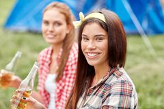 Happy young women with tent and drinks at campsite Royalty Free Stock Photography