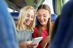Happy young women in travel bus with smartphone. Transport, tourism, road trip and people concept - happy young women or friends in travel bus texting or reading Royalty Free Stock Photo