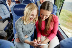 Happy young women in travel bus with smartphone. Transport, tourism, road trip and people concept - happy young women or friends in travel bus texting or reading Royalty Free Stock Images