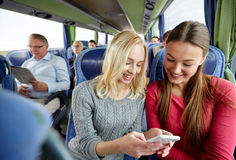 Happy young women in travel bus with smartphone Royalty Free Stock Photography