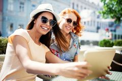Happy young women using digital tablet in cafe outdoor royalty free stock images