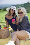 Happy young women using smart phone at picnic. Stock Image