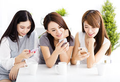 Happy young women watching smart phone in living room royalty free stock photo
