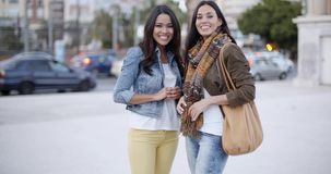Happy young women waving at the camera. Two trendy happy young women standing in an urban street waving at the camera with vivacious smile of pleasure stock footage