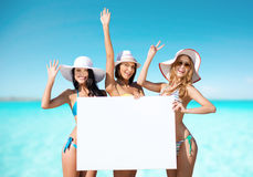Happy young women with white board on summer beach Royalty Free Stock Images