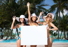 Happy young women with white board on summer beach Stock Photography