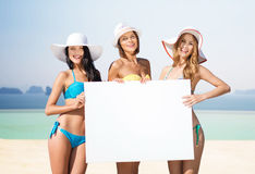 Happy young women with white board on summer beach Royalty Free Stock Image