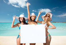 Happy young women with white board on summer beach Stock Images