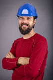 Happy young worker with hardhat and arms folded blinking Royalty Free Stock Image
