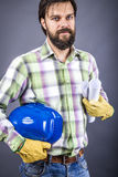 Happy young worker with hardhat and gloves posing. Over gray background Stock Photo