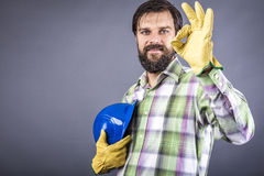 Happy young worker with hardhat and gloves showing ok sign Stock Image
