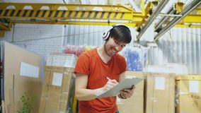 Happy young worker in industrial warehouse listening to music and dancing during work. Man in headphones have fun at. Happy young worker in industrial warehouse Royalty Free Stock Photos
