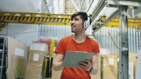 Happy young worker in industrial warehouse listening to music during work. Man in headphones have fun at workplace. Happy young worker in industrial warehouse royalty free stock photos