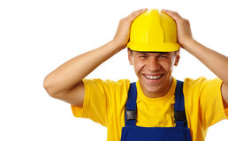 Happy young worker put his hands on hard hat Stock Image