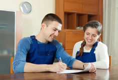 Happy young  workers in uniform with financial documents at tabl Stock Image