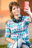 Happy young wpman taking pictures of herself Royalty Free Stock Photography