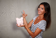 Happy youngster pointing a piggy bank. Happy youngster in tank top pointing a piggy bank while looking at camera Stock Photography
