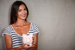 Happy youngster smiling while holding a piggy bank Stock Photos