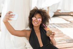 Happy youthful african girl relaxing with gadget on beach Stock Image