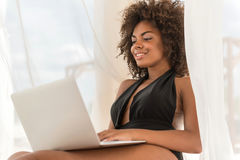 Happy youthful african woman using gadget on summer resort Stock Photo