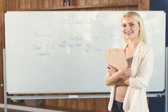 Happy youthful girl learning new job strategies in office Royalty Free Stock Image