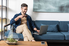 Happy youthful guy browsing internet via notebook in living room Royalty Free Stock Photo